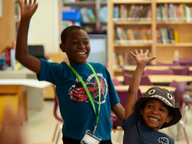 Two boys wave their hands with excitement in a library
